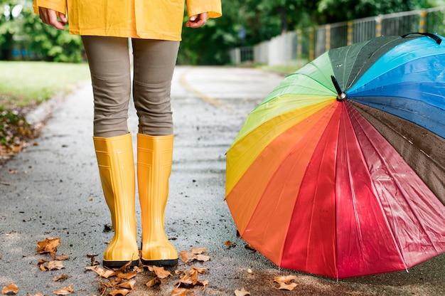 Frau in den regenstiefeln, die neben buntem regenschirm stehen