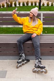 Frau in den rollenblättern, die ein selfie auf bank nehmen