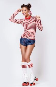 Frau in den rollschuhen und mit roten kopfhörern und lutscher
