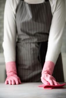 Frau in den rosafarbenen gummischutzhandschuhen, die staub abwischen und schmutzig. reinigungskonzept, textfreiraum