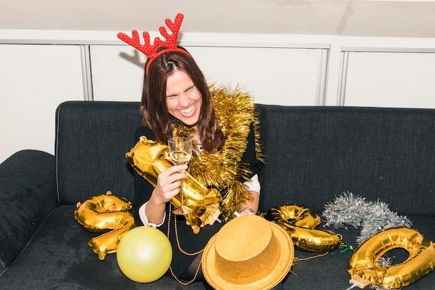Frau in den rotwildhörnern, die auf couch mit champagner sitzen