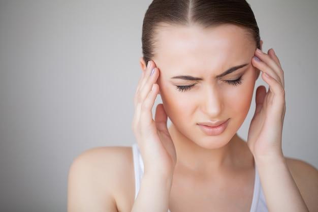 Frau in den schmerz, die schlecht und krank sich fühlen, kopfschmerzen und fieber habend und halten hand auf stirn. schönes unglückliches müdes mädchen, das unter schmerzlichem hauptschmerz und druck leidet. gesundheitswesen. hohe auflösung