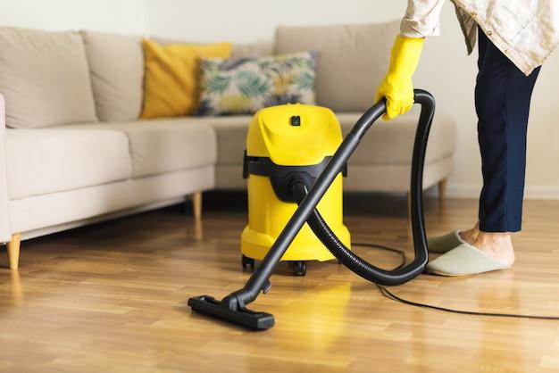 Frau in den schutzhandschuhen, die das wohnzimmer mit gelbem staubsauger säubern. sauberes konzept
