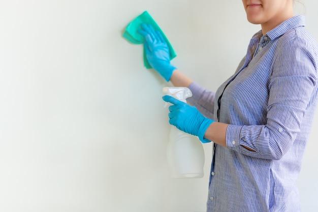 Frau in den schutzhandschuhen, die staub unter verwendung eines sprays und eines staubtuchs beim säubern ihres hauses abwischen.