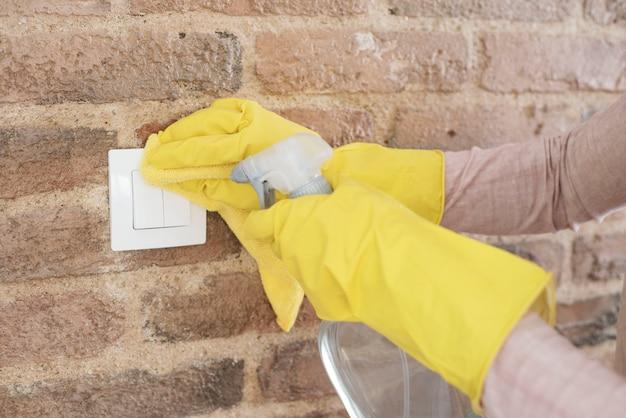 Frau in den schutzhandschuhen, die wandschalter desinfizieren, während sie zu hause reinigen