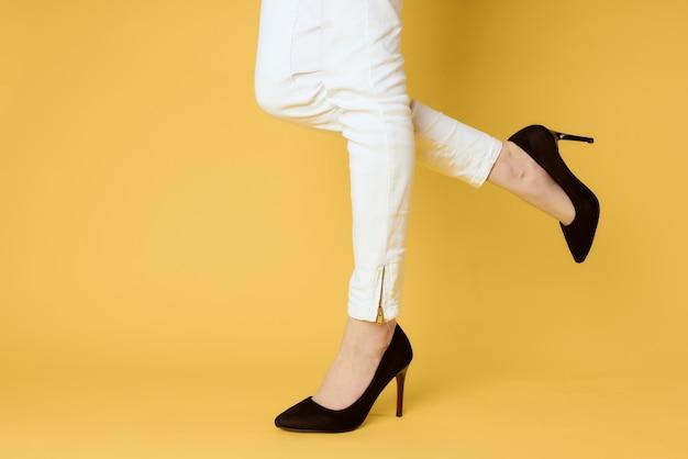 Frau in den schwarzen schuhbeinen beschnitten beleuchtete gelbe modeeinkäufe.