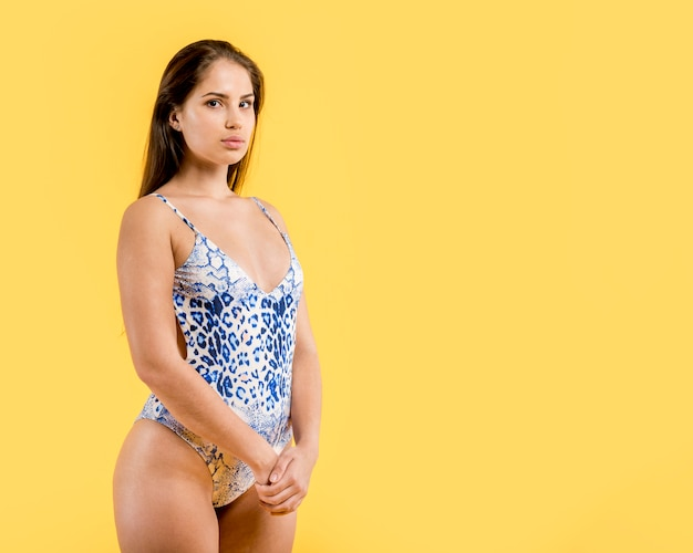 Frau in den stehenden händen des blauen badeanzugs umklammert