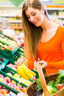 Frau in den supermarkteinkaufslebensmitteln