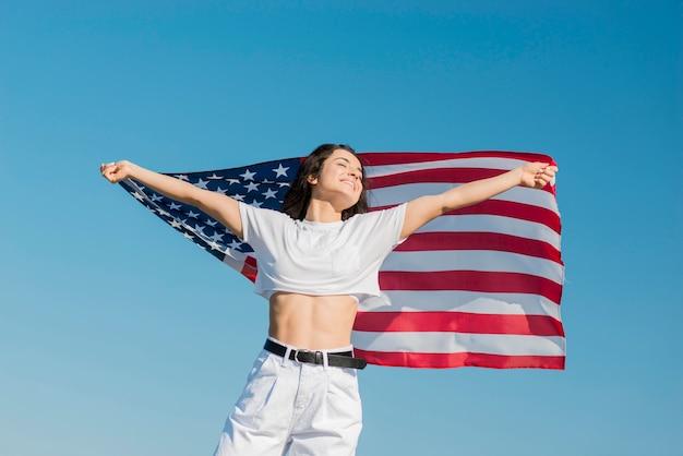 Frau in den weißen kleidern, die große usa-flagge halten