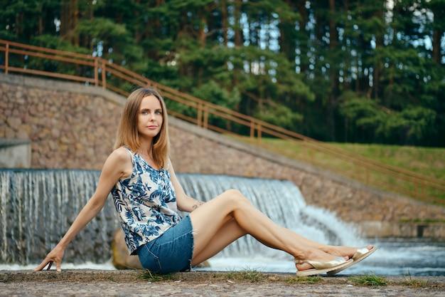 Frau in der ärmellosen bluse und im jeansrock, die ruhe auf dem landerholungsgebiet haben und nahe künstlichem wasserfall sitzen
