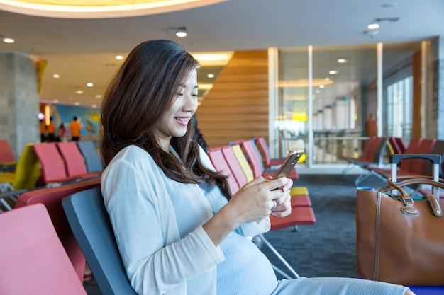 Frau in der aiport lounge, die im stuhl am fenster und uns sitzt