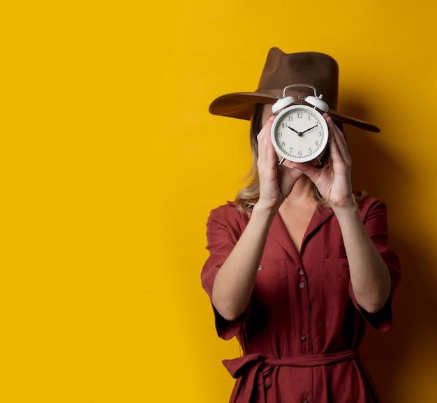 Frau in der artkleidung der vierziger jahre mit wecker