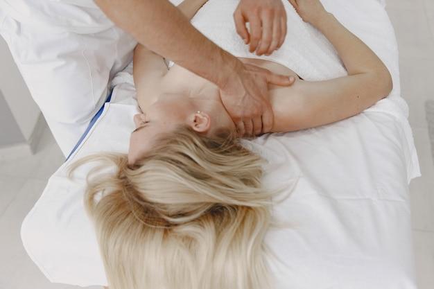 Frau in der arztpraxis. der physiotherapeut rehabilitiert den rücken.