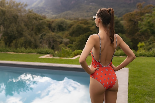 Frau in der badebekleidung, die mit den händen auf hüfte nahe poolside im hinterhof steht