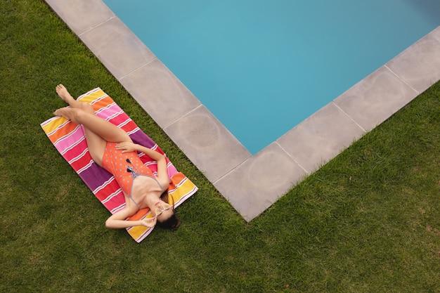 Frau in der badebekleidung, die nahe poolside im hinterhof sich entspannt