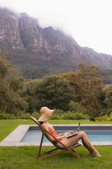 Frau in der badebekleidung unter verwendung des laptops auf einem sonnenruhesessel nahe poolside im hinterhof