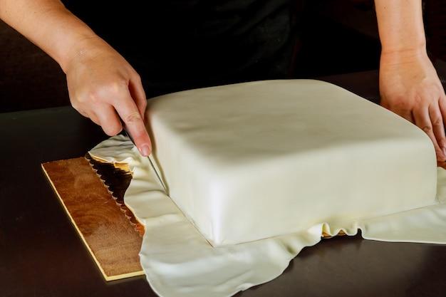 Frau in der bäckerei, die weißen fondant der hochzeitstorte bedeckt