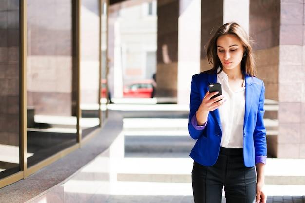 Frau in der blauen jacke überprüft ihr telefon
