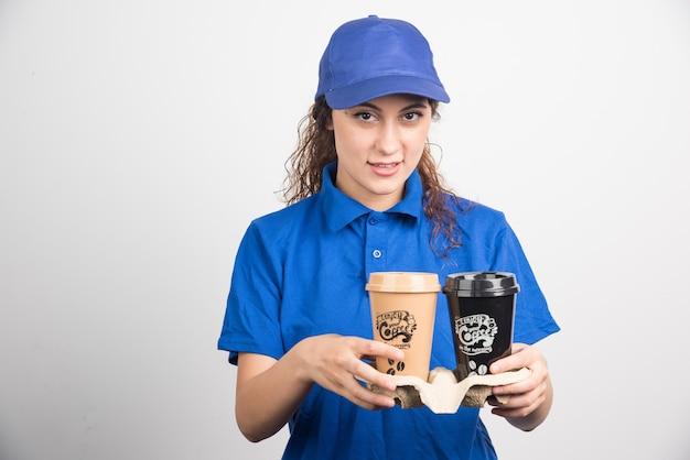Frau in der blauen uniform, die zwei tassen kaffee auf weißem hintergrund hält. hochwertiges foto