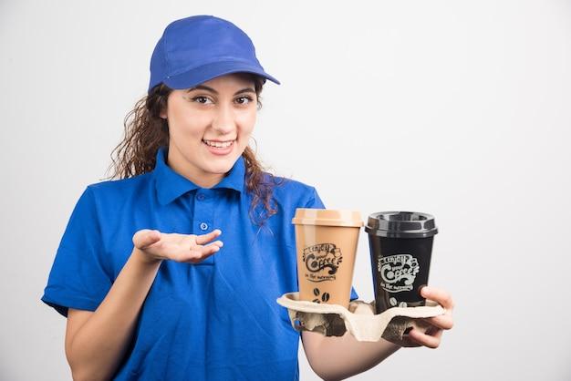 Frau in der blauen uniform zeigt auf zwei tassen kaffee auf weißem hintergrund