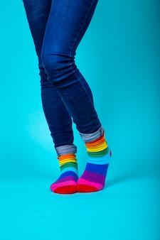 Frau in der blue jeans, die ihre beine mit lgtb kreuzt, färbte socken
