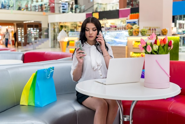 Frau in der cafeteria mit laptop, telefon und dollar