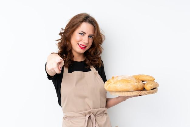 Frau in der chefuniform. der weibliche bäcker, der eine tabelle mit einigen broten hält, zeigt finger auf sie mit einem überzeugten ausdruck