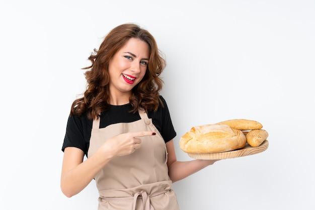 Frau in der chefuniform. weiblicher bäcker, der eine tabelle mit einigen broten hält und sie zeigt