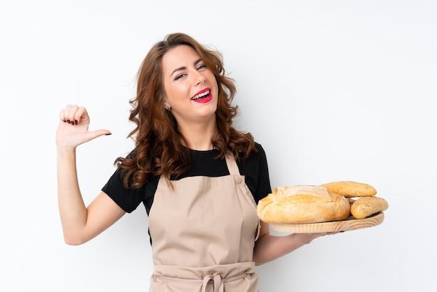 Frau in der chefuniform. weiblicher bäcker, der eine tabelle mit einigen broten stolz und selbstzufrieden hält