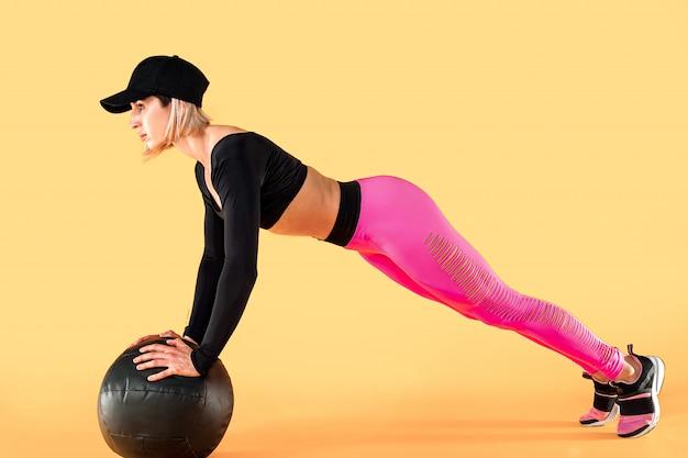 Frau in der eignungskleidung ausbildend mit einem medizinball. weiblicher athlet, der unterleibstraining unter verwendung eines medizinballs tut.