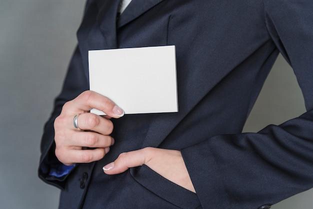Frau in der eleganten jacke, die leeres papier hält