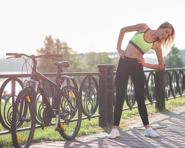 Frau in der fitnesskleidung, die aufwärmübungen macht