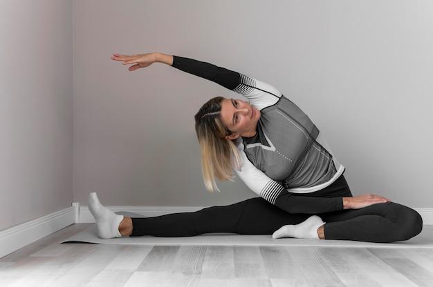 Frau in der fitnesskleidung, die übungen macht