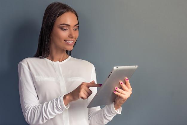 Frau in der formalen kleidung benutzt eine digitale tablette.