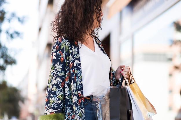 Frau in der freizeitkleidung, die mit einkaufstaschen steht