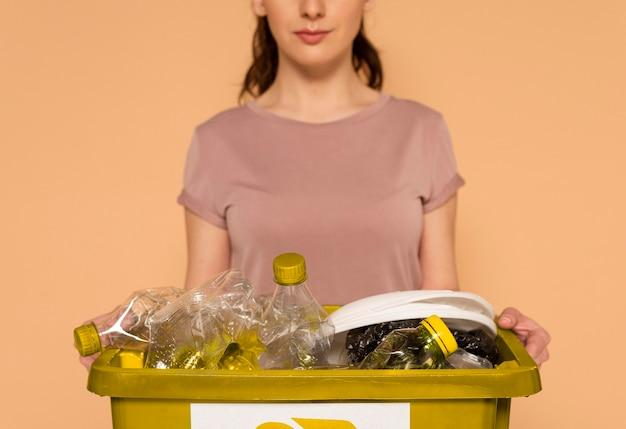 Frau in der freizeitkleidung, die wiederverwendbare recyclingbox trägt