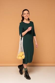 Frau in der freizeitkleidung, die wiederverwendbare schildkrötenbeutel trägt