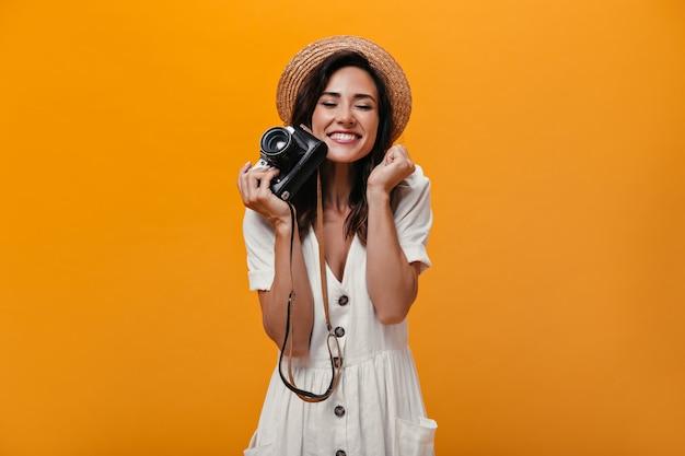 Frau in der freudigen stimmung, die retro-kamera auf orange hintergrund hält. wunderbares mädchen in der leichten stilvollen kleidung und im strohhut, die aufwerfen.