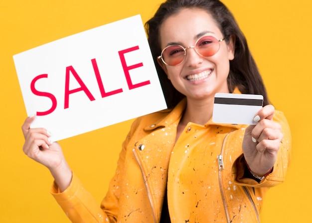 Frau in der gelben jacke bereit zum einkaufen