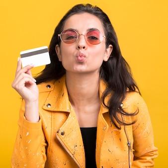 Frau in der gelben jacke, die einen kuss bläst