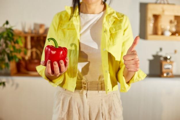 Frau in der gelben jacke, die frischen roten pfeffer hält und daumen auf geste auf der küche macht