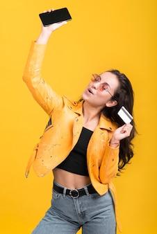 Frau in der gelben jacke, die ihr handy in der luft hält