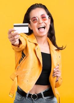 Frau in der gelben jacke, die ihre einkaufskarte zeigt