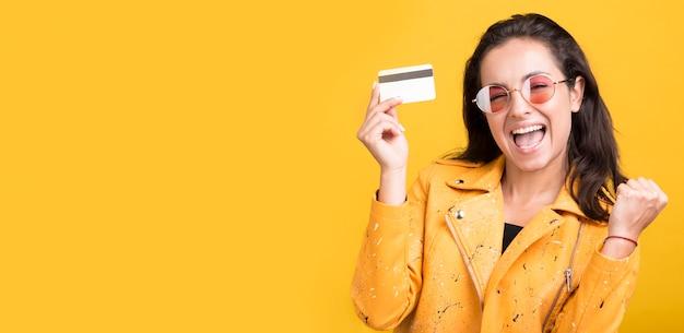 Frau in der gelben jacke, die kreditkartenkopierraum hält