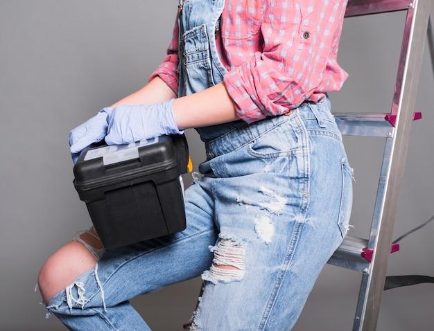 Frau in der gesamtheit auf leiter mit werkzeugkasten