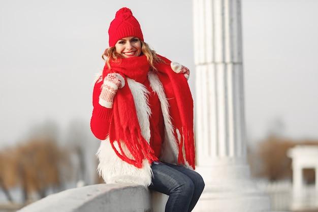 Frau in der gestrickten wintermütze und im schal, die kamera mit lächeln betrachten