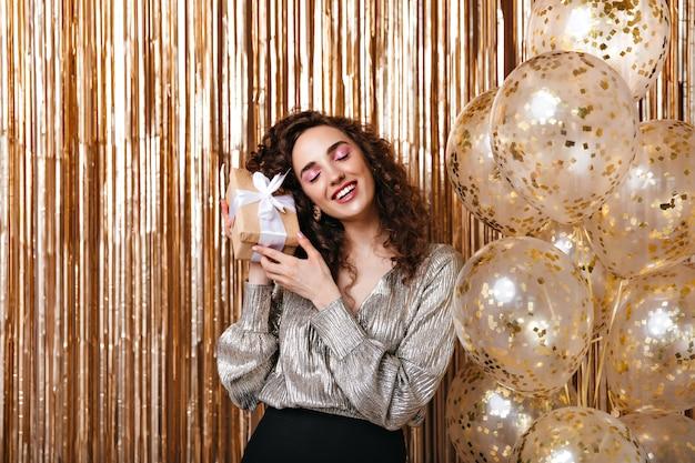 Frau in der glänzenden bluse, die geschenkbox mit weißer schleife auf goldenem hintergrund hält