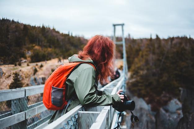 Frau in der grauen jacke und im orangefarbenen rucksack, die schwarze dslr-kamera halten
