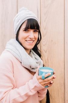 Frau in der grauen kappe mit kaffeetasse