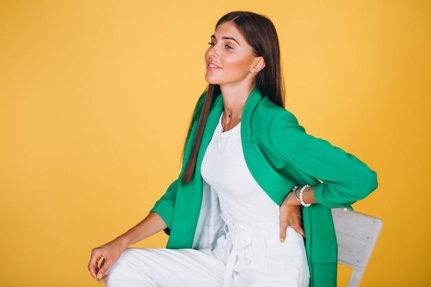 Frau in der grünen jacke, die auf stuhl auf gelbem hintergrund sitzt